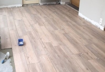 Afwerken van herstelling met nieuwe vloer op vraag van de klant